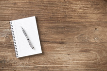Note Pad And Pen On Wooden Table