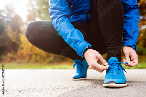 Fotomural  Unrecognizable runner crouching, tying shoelaces, close up