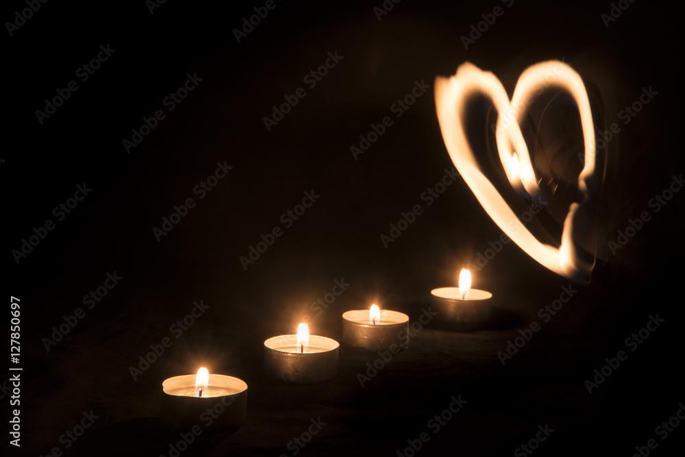 Fototapeta Burning candles against black background