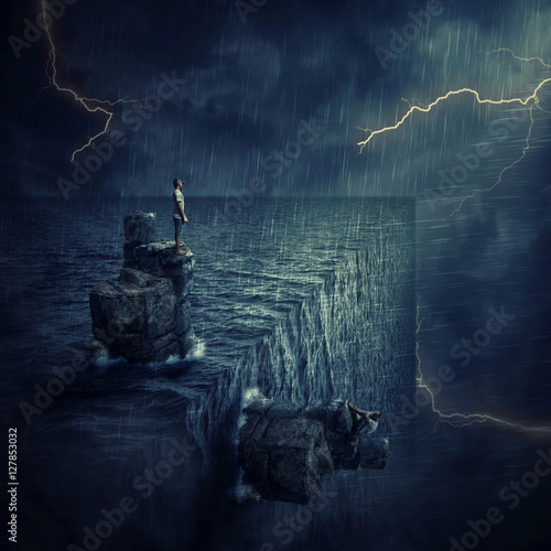 Conceptual image with a lost man sitting on a rock cliff island, in the middle of the ocean, try to find himself in a parallel world, alternate reality Tablou Canvas