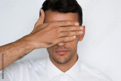 Fotografie, Obraz  Close-up portrait of a handsome caucasian man cover eyes with hand isolated on gray background