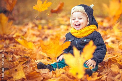 Plakat mały chłopiec w parku jesienią