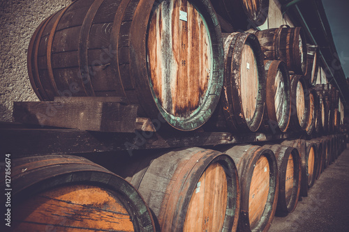 Photo wooden barrels in the distillery folded in the yard in shelves