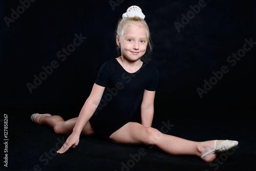Tuinposter Gymnastiek Beautiful sport training girl portrait in leotard in nhe black room. classic portrait of gymnastics girl