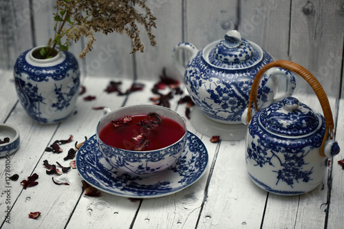 Fotografie, Obraz  Set of decorative porcelain dishes, cups, plates, teapot with blue ethnic pattern in the style of Chinese painting with red karkade tea