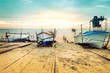 Old fishing boats laid over the sea shore. Colorful sunset above the sandy beach in Ravda, Bulgaria.