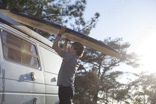 Photo  An adult man putting a surfboard on top of a van