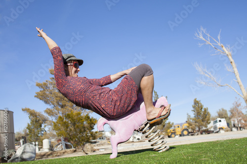 Fotografie, Obraz  An adult woman playing cowgirl with a stylish playground performance near Lone Pine, California