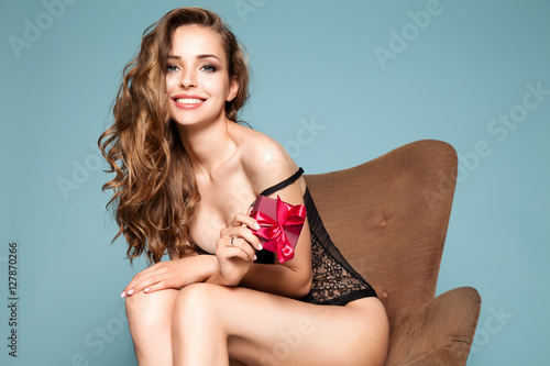 Photo  Beautiful young woman in black lingerie with gift box in hands on a pink backgro