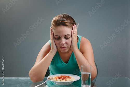 Portrait of woman with no appetite in front of the meal Wallpaper Mural