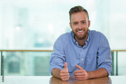 Photo Smiling Man Sitting at Cafe Table and Gesturing