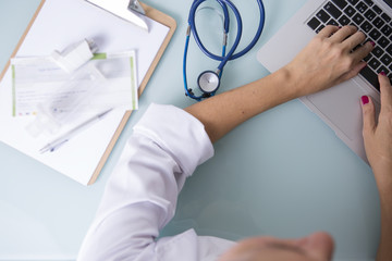 Female hands of a doctor working on laptop