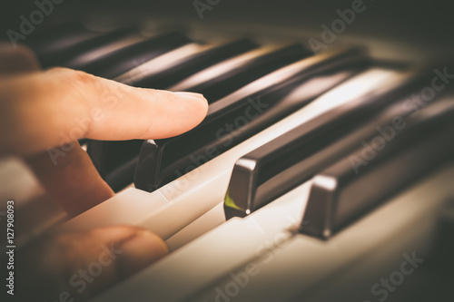 Plakat palce męskiego muzyka grającego na klawiszach fortepianu