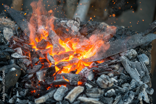 Valokuva  Blacksmith heats a blank for the knife in hot coals in the forge, close-up