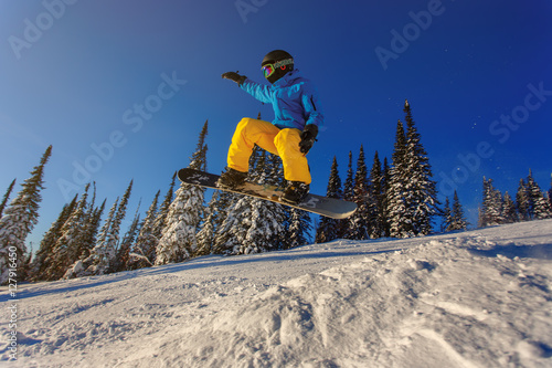 Fotografiet  Snowboarder jumping against blue sky