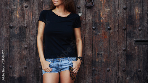 Fotografía  A cropped photo of a young woman wearing black blank t-shirt and blue jeans shorts standing on the wooden door background