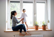 canvas print picture - Mother with her little daughter looking out of window