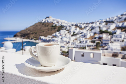 Traditional greek coffee on a balcony with beautiful greek mediterranean town on the background. Vacations in Greece