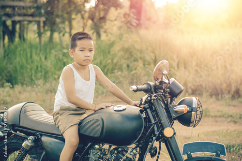 Photo  Little kid  on classic motocycle in park.
