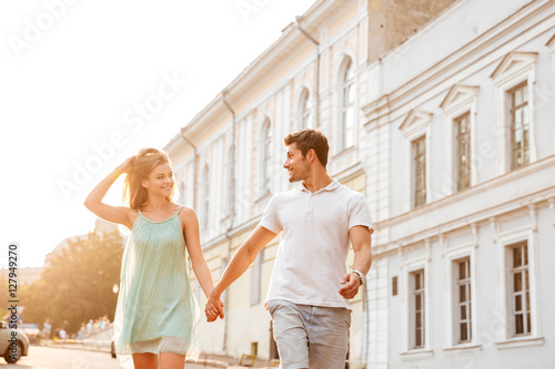 Fotografia, Obraz  Happy romantic young couple in love walking and holding hands