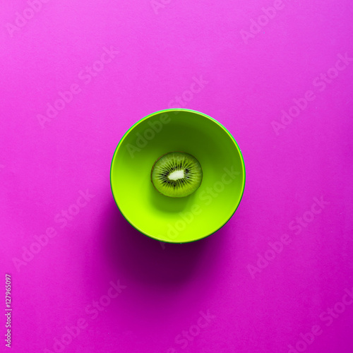 Lime in green bowl on purple background. - 127965097
