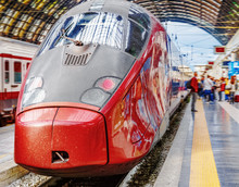 Trenitalia Frecciarossa (red Arrow) On Platform Of Milan Central Station. This High Speed Train Can Reach 300 Km/h And Operate Turin-Milan-Bologna-Florence-Rome-Naples Route. Passanger Staying Nearby.