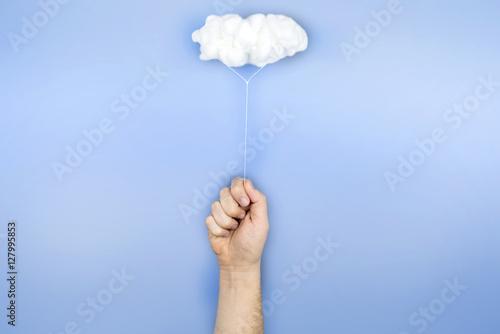 Fotografie, Obraz  Mano sujetando una nube que hace de globo sobre fondo azul.