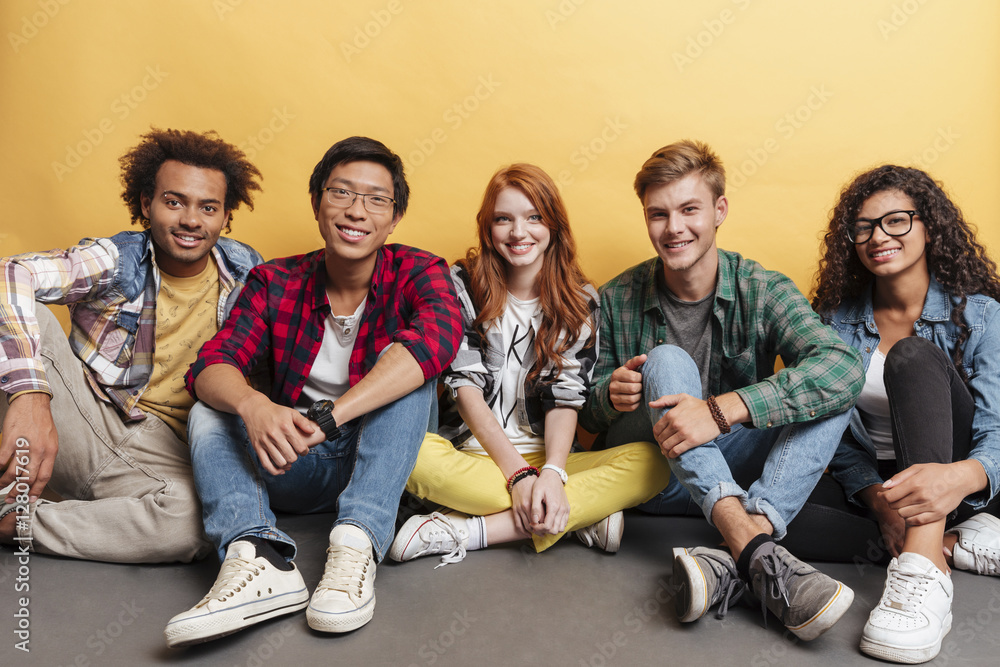 Fototapety, obrazy: Multiethnic group of smiling friends sitting on the floor together