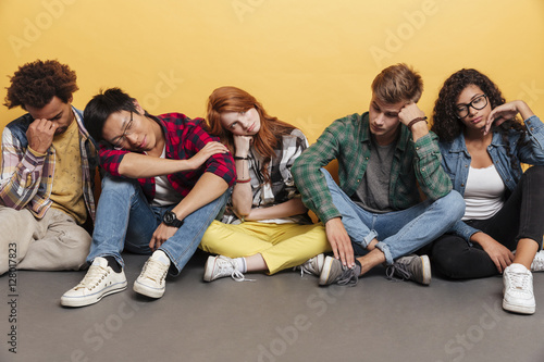 multiethnic group of exhausted young friends sitting and sleeping