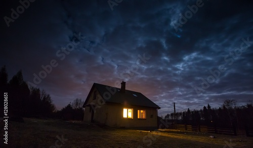 Foto op Canvas Nacht Landscape with house at night under cloudy sky