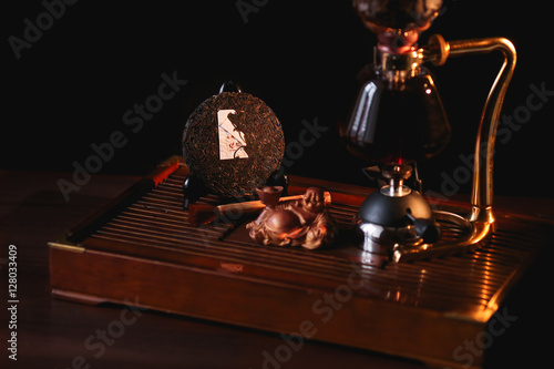 Photo  Puer tea in the siphon with extruded pancake Shu Puer and Buddha statue on black background