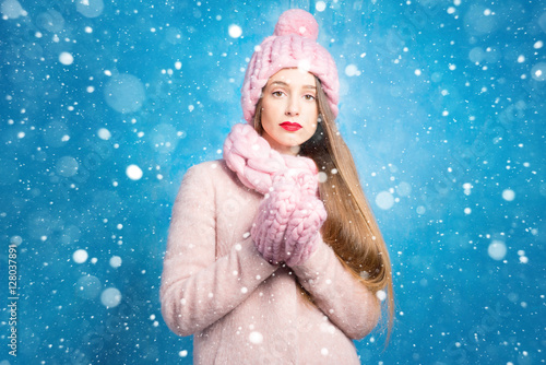 Poster Winter portrait of a sad woman in knitted pink scurf, gloves and hat on the blue