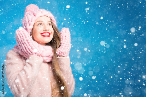 Photo sur Toile Carnaval Winter portrait of a beautiful woman in knitted pink scurf, gloves and hat with snow flake on the blue background
