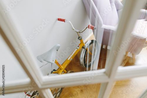 Deurstickers Fiets A vintage yellow kids bike in a living room seen through a glass door.