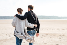 Back View Of A Young Casual Couple Walking Along Beach