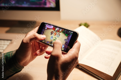 Obraz Man hands playing videogames on cell phone in the evening - fototapety do salonu