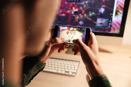 Plakat  Closeup of man playing videogame on smartphone in evening