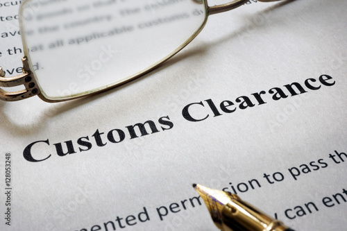 Fotografía  Page of paper with words Customs Clearance and glasses.