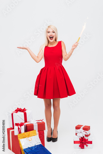 Fotografija  Excited woman in red dress holding flapper and having fun