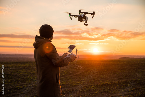 Obraz Man operating a drone with remote control. Dark silhouette against colorful sunset. Soft focus. - fototapety do salonu