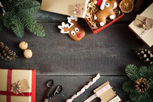 Christmas Background With Decorations, Gift Boxes, Ribbon And Ginger Bread On Wooden Board.