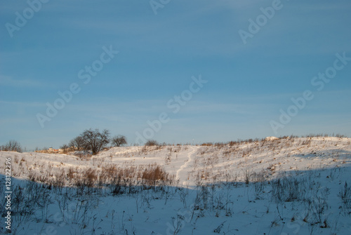 Foto op Aluminium Blauw Beautiful winter landscape with snow-covered hills at sunset