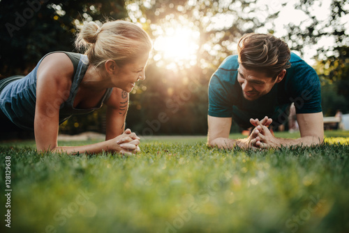 Fotografiet  Fit young man and woman exercising in park