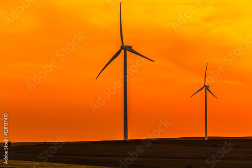 Deurstickers Oranje eclat Wind turbines on an agricultural field in the sunset