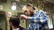 Attractive young barber is cutting human hair with the scissors. He is looking at hair with concentration. The bearded man is raising his chin