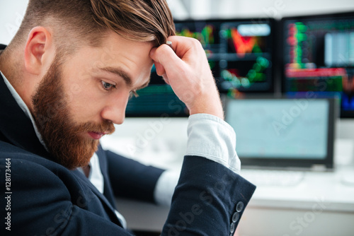 Pensive bearded young businessman sitting and thinking in office Poster