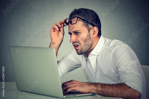 Photo man with glasses having eyesight problems confused with laptop software