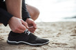 Man is tying shoelace while standing on the sand