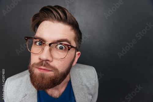 Portrait of curious bearded young businessman in glasses
