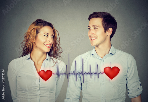 man woman looking at each other with red hearts linked by cardiogram Wallpaper Mural